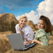 Country girls resting with laptop - Stock Photo
