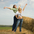 Stock Photo: Girls standing on hay