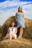 Farm girls resting on hay — Stock Photo