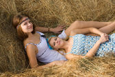 Country girls resting on hay — Stock Photo