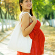 Pregnant woman on summer alley — Stock Photo #7599165