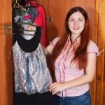 Woman chooses dress at wardrobe — Stock Photo