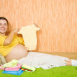 Pregnant woman with baby&#039;s clothes - Stock Photo