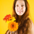 Stock fotografie: Girl with flowers over yellow