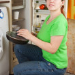 Woman putting griddle into fridge — Stock Photo #7599332