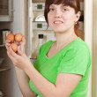 Woman putting fresh eggs into fridge - Stock Photo