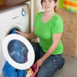Woman loading the washing machine - Stock Photo
