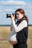 Pregnant woman taking photo — Stock Photo