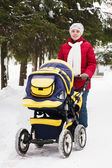 Mother with perambulator in wintery park — Photo