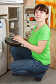 Woman putting griddle into fridge — Stock Photo