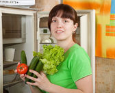Woman putting fresh vegetables into fridge — Stock Photo