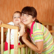 Happy mother with baby   in crib - Stock Photo