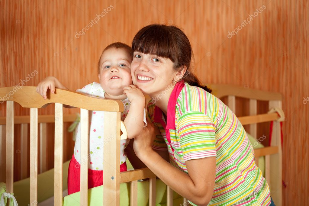 Happy mother with baby of one year old  in crib  Stock Photo #7609923