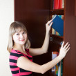 Stock Photo: Woman selecting book in bookcase