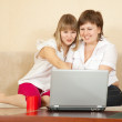 Happy women using laptop in home - Foto Stock