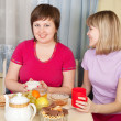 Girls  drinking tea and gossiping in home - Foto Stock