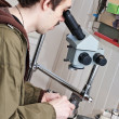Foto Stock: Jeweller is working with microscope