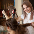 Hairdresser works on woman hair - Stock Photo