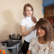 Hairdresser works on woman hair - Foto Stock