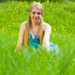 Blonde girl sits in grass — Stock Photo