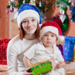 Mother and little son with Christmas gift - Stock Photo