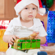Boy sits with  Christmas gift - Stock Photo