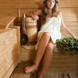 Woman  on wooden bench in sauna - Stock Photo