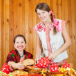 Women in traditional clothes with pancake — Stock Photo #7613306