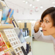 Woman chooses mascara at cosmetics shop — Stock Photo #7613317