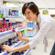 Woman chooses  cosmetic  at cosmetics  shop — Foto de Stock