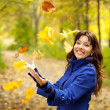 Girl  throw up maple leaves - Stock Photo