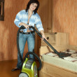 Foto Stock: Womcleaning with vacuum cleaner