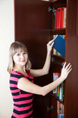 Woman selecting book in bookcase — Stock Photo