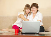 Happy women using laptop in home — Stok fotoğraf