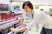 Woman chooses cosmetic at cosmetics shop — Stock Photo