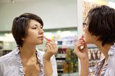 Mujer prueba el lápiz labial — Foto de Stock