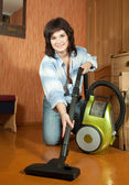 Sexy girl cleans with vacuum cleaner — Stock Photo