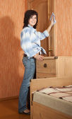 Happy girl dusting at home — Stock Photo