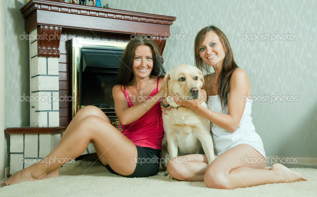 Two mid adult women with  Labrador retriever  near   fireplace — Stock Photo #7613587