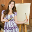 Girl near easel with canvas. — Stock Photo