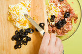 Adds grated eggs and sliced olives in mince — Stock Photo