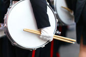 Drum with a hand and drumsticks on parade — Stock Photo
