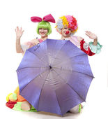 Clowns behind an umbrella wave hands at parting — Стоковое фото