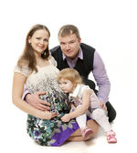 The man and the pregnant woman sit the little girl listens to a stomach of the woman — Stock Photo