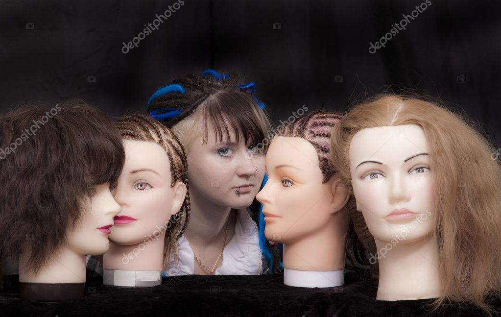 Portrait of the girl amongst mannequin on black background — Stock Photo #7419305