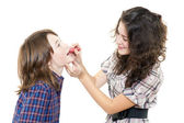 Senior girl dyes younger lip by pomade — Stock Photo