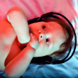 Small baby listening to music - Stock Photo