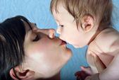 Happy mother kissing the baby — Stock Photo