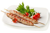 Kebabs served with tomatoes — Stock Photo