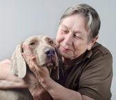 Senior woman hugging and comforting dog — Stockfoto
